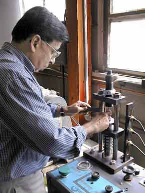 Dr. Deepak Kapur operating a Corbin Hydro-Press in Building 1609